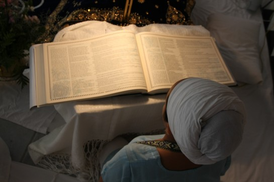 Spanish translation of  hukam being read from the Siri Guru Granth Sahib